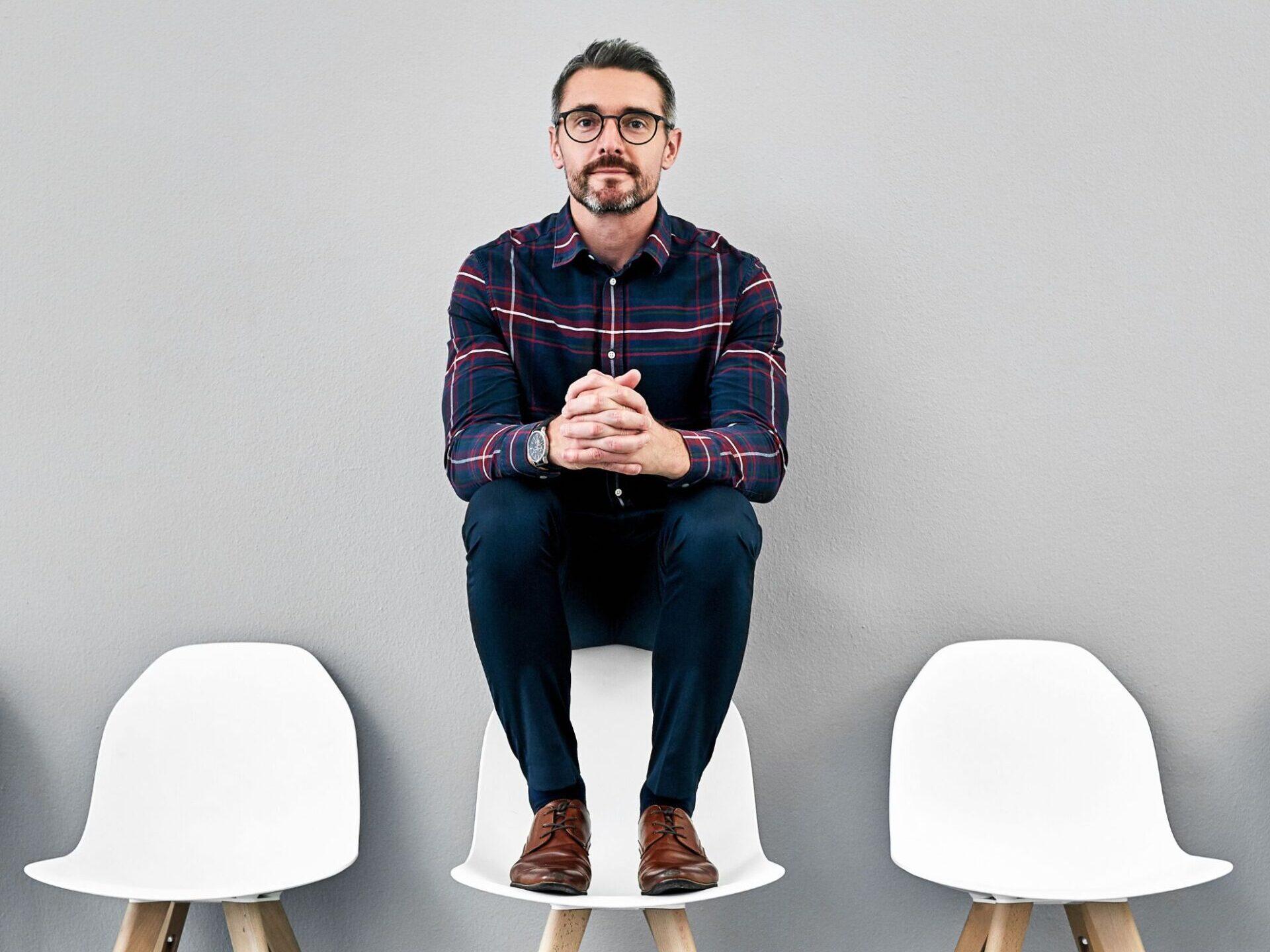 Mand der sidder på stoleryg